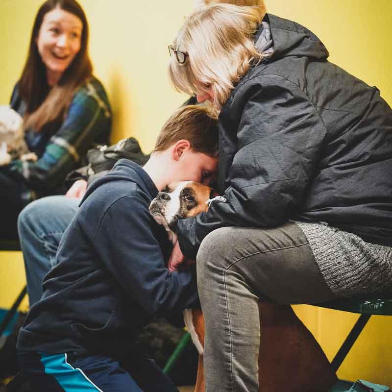 boy-hugging-dog-with-mom